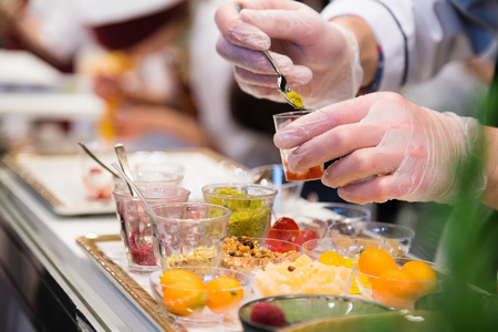 Chef wearing white gloves and standing behind full lunch service station with assortment of food