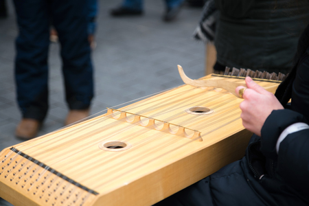 Girl performing music with traditional string instrument at the fare on the street Stock Photo