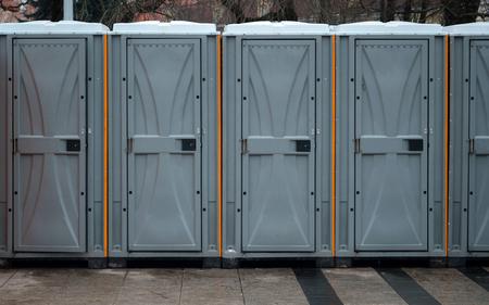 Lunga fila di bagni mobili fuori città. Servizi igienici bio all'aperto Archivio Fotografico
