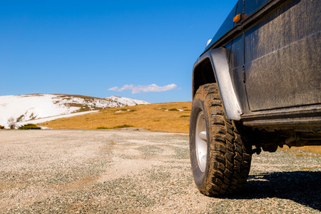Off road 4x4 car in the snowy mountains on a sunny day. Off-road traveling, all terrain vehicle in nature Foto de archivo