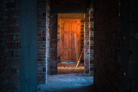 Old, scary, abandoned house interior. Wooden door at the end of scary concrete corridor. Architecture structure Stock Photo