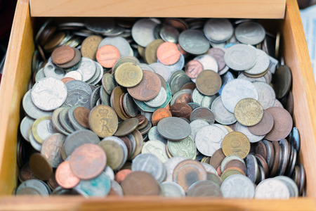 Close up view of different countries coins in a wooden box. Various metal coins background