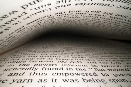 Dentro del concepto de libro. Letras latinas y palabras en un libro abierto con fondo dramático negro. Educación, concepto de conocimiento