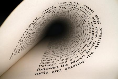 Im Buchkonzept. Lateinische Buchstaben und Wörter auf einer tunnelförmigen, perspektivischen Buchseite mit schwarzem dramatischem Licht. Bildung, Wissenskonzept