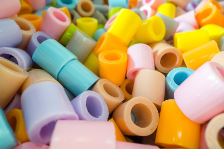 Short plastic tube pieces stacked on top of each other. Plastic waste and recycling concept