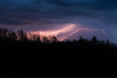 Colourful summer thunder storm over the forest at night. Spectacular lighting strikes in the sky Standard-Bild - 124897916