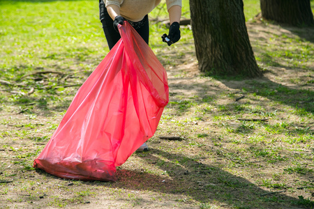 Woman volunteer wearing picking up trash and plastic waste in public park. Young girl wearing gloves and putting litter into red plastic bag outdoors
