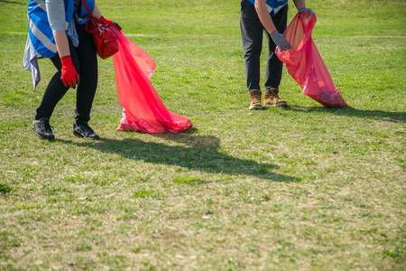 Man and woman volunteer wearing picking up trash and plastic waste in public park. Young people wearing gloves and putting litter into red plastic bags outdoors
