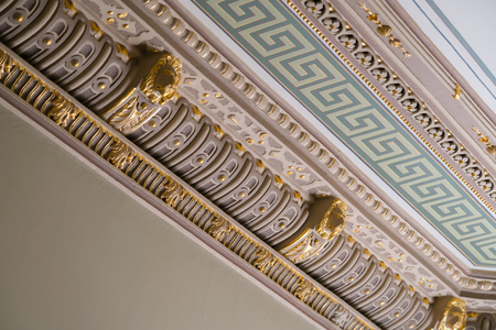 Stucco and luxurious decorative elements on ceiling. Luxury aesthetic in a home decor. Golden lion head pieces on a ceiling