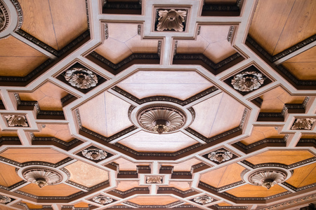 Luxurious antique wooden ceiling decorations in an old minor. Expensive geometric shapes made of hard wood