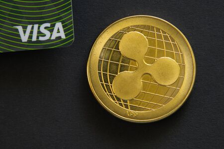 PRAGUE, CZECH REPUBLIC - May, 2019: Golden Ripple coin next to Visa bank card on black background. Digital currency, block chain market