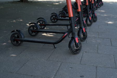 Modern eco electric city scooters for rent outdoors on the sidewalk. Alternative tourism, transportation around the city, bike replacement service. E-scooters can be rented with an app