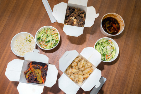 Top view of Chinese take away food with chop sticks on wooden table. Spicy asian food in white box - salad, souse, rice with egg, dry beef, crunchy chicken cooked in oil. Reklamní fotografie - 124898179