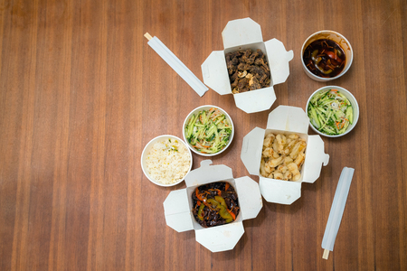 Top view of Chinese take away food with chop sticks on wooden table. Spicy asian food in white box - salad, souse, rice with egg, dry beef, crunchy chicken cooked in oil. Stock Photo