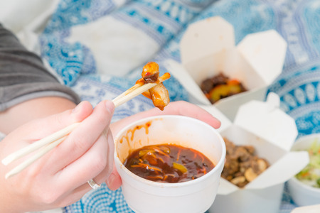 Eating Chinese take away food with chop sticks at home with bed sheets in the background. Spicy asian food in white box - salad, souse, beef, chicken cooked in oil Stock Photo