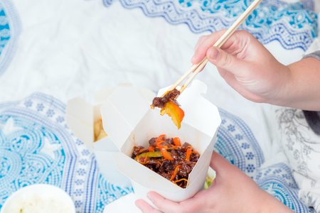 Eating Chinese take away food with chop sticks at home with bed