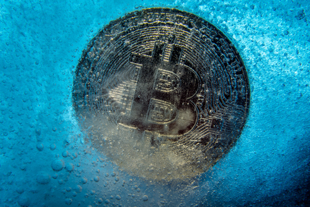 Silver Bitcoin, bit coin online digital currency frozen in the blue ice. Concept of block chain, crypto market crash. Frozen crypto money, depreciation Standard-Bild - 124898197
