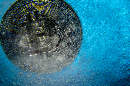 Silver Bitcoin, bit coin online digital currency frozen in the blue ice. Concept of block chain, crypto market crash. Frozen crypto money, depreciation Reklamní fotografie
