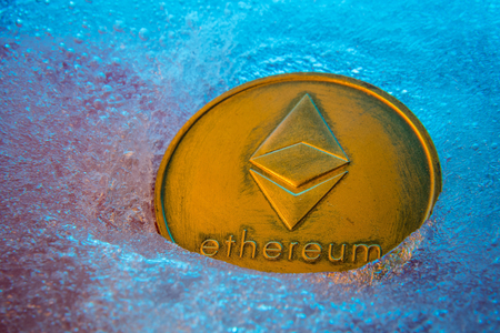 Golden Ethereum coin, online digital currency frozen in the blue ice. Concept of block chain, market crash. Frozen crypto money, depreciation