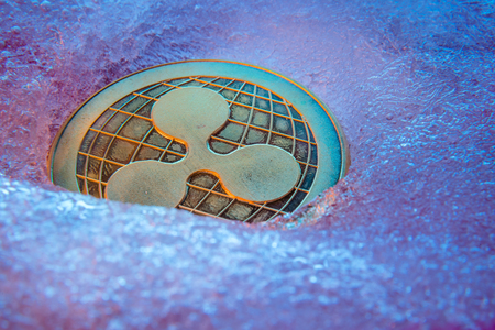 Golden Ripple coin, online digital currency frozen in the blue ice. Concept of block chain, market crash. Frozen crypto money, depreciation