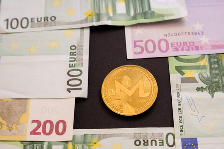 Ripple coin next to Euro bank notes on black background. Digital currency, block chain market. Euro bills next to crypto coin