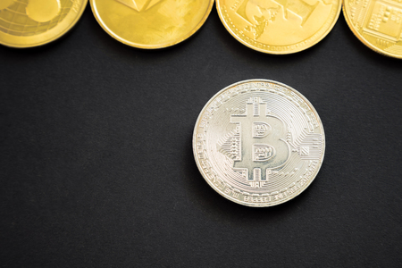 Silver bitcoin crypto currency coin next to others: Litecoin, Ripple, Monerd, Ethereum coin on black background. Digital currency, block chain market Фото со стока