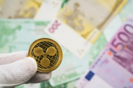 Man in white cloves holding Ripple coin between fingers with Euro bank notes in the background. Digital currency, block chain market