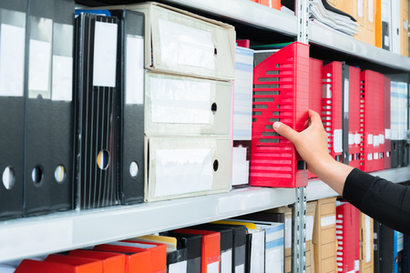 Mans hand picking a blank blind folder with files from the shelf. Archival, stacks of documents at the office or library Stock Photo