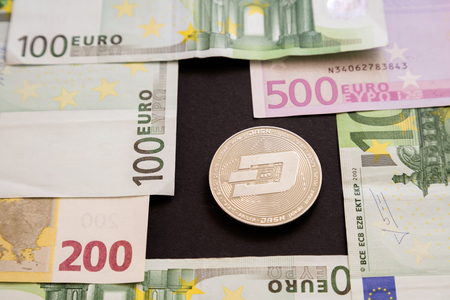 Silver Dash coin next to Euro bank notes on black background. Digital currency, block chain market. Euro bills next to crypto coin