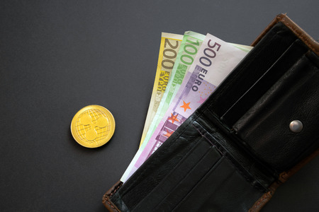 Ripple coin next to Euro bank notes sticking out of a wallet on black background. Digital currency, block chain market. Euro bills next to crypto coin Stock Photo