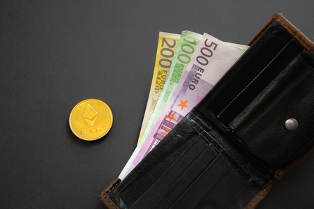 Ethereum coin next to Euro bank notes sticking out of a wallet on black background. Digital currency, block chain market. Euro bills next to crypto coin Stock Photo