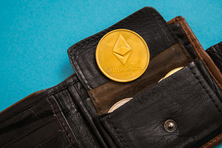Ethereum coin sticking out of leather wallet o blue background. Digital currency, block chain market.