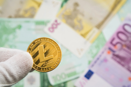 Man in white cloves holding Litecoin coin between fingers with Euro bank notes in the background. Digital currency, block chain market Stock Photo