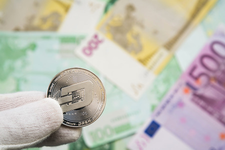 Man in white cloves holding Dash coin between fingers with Euro bank notes in the background. Digital currency, block chain market