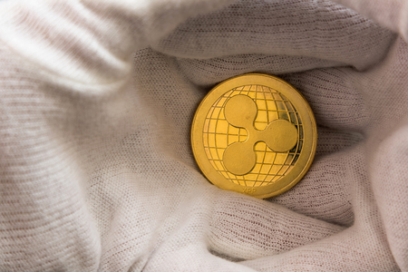 Man in white cloves holding Ripple coin between hand palms. Digital currency, block chain market