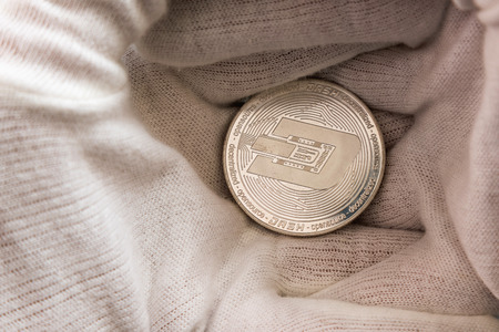 Man in white cloves holding Dash coin between hand palms. Digital currency, block chain market Stock Photo - 124898476