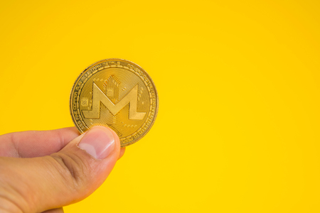 Business man hand holding Monerd coin between fingers on yellow background. Digital currency, block chain market, online business