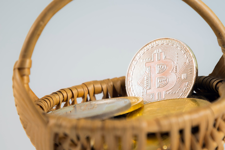 Circle Bitcoin coin in the wicker basket on white background. Digital currency, block chain market, online business Stock Photo