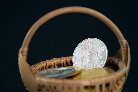 Circle Bitcoin coin in the wicker basket on black background. Digital currency, block chain market, online business Stock Photo