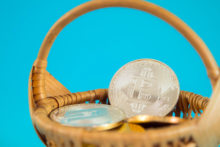 Circle Bitcoin coin in the wicker basket on blue background. Digital currency, block chain market, online business