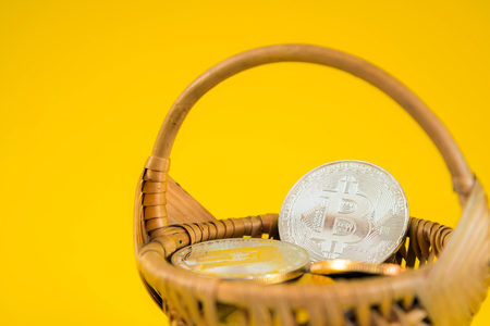 Circle Bitcoin coin in the wicker basket on yellow background. Digital currency, block chain market, online business