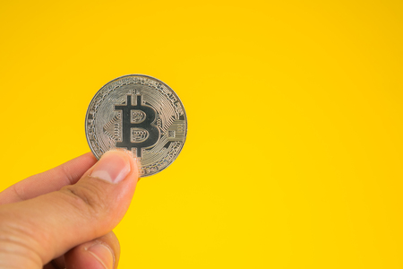 Business man hand holding Bitcoin between fingers on yellow background. Digital currency, block chain market, online business