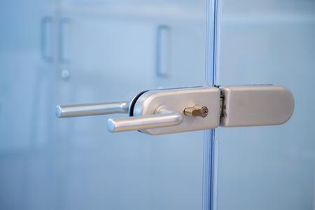 Modern, contemporary glass door lock handle in modern business office.