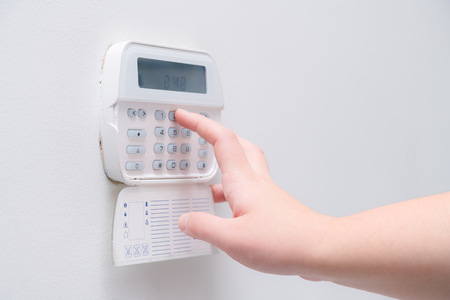 Woman hand entering alarm system password of an apartment, house of business office. Surveillance and protection console against rubbery and thief 스톡 콘텐츠