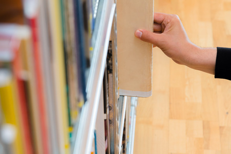 Young student picking a book from the shelf in the library. Preparing for exams, young man searching for or choosing a book in the public library in university Stock Photo
