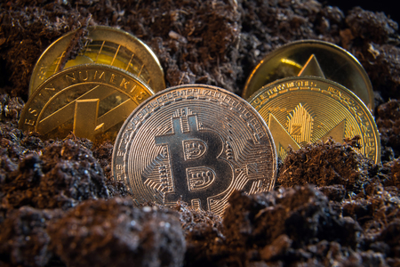 Silver bitcoin crypto currency coin in the dirt ground with others in the back: Litecoin, Ripple, Monerd, Ethereum coin. Digital currency, block chain market, online business Stock Photo
