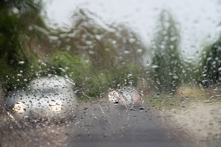 Rain drops on front car window, driving in heavy rain. Pouring rain, water drops on window. Concept of windshield not working, dangerous driving conditions