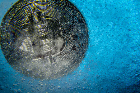 Silver Bitcoin, bit coin online digital currency frozen in the blue ice. Concept of block chain, crypto market crash. Frozen crypto money, depreciation Stock Photo
