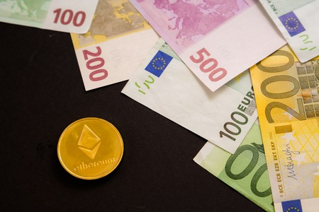 Ethereum coin next to Euro bank notes on black background. Digital currency, block chain market. Euro bills next to crypto coin Stock Photo - 124898741