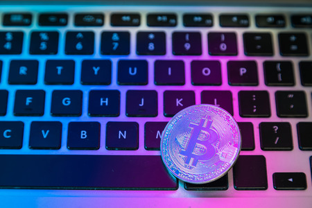 Circle Bitcoin coin on top of computer keyboard buttons. Digital currency, block chain market, online business